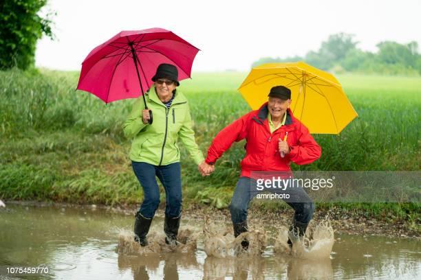 heureux aînés drôles bénéficiant de journée sous la pluie - pluie humour photos et images de collection