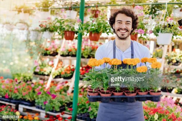 Jardinero feliz con bandeja de flores