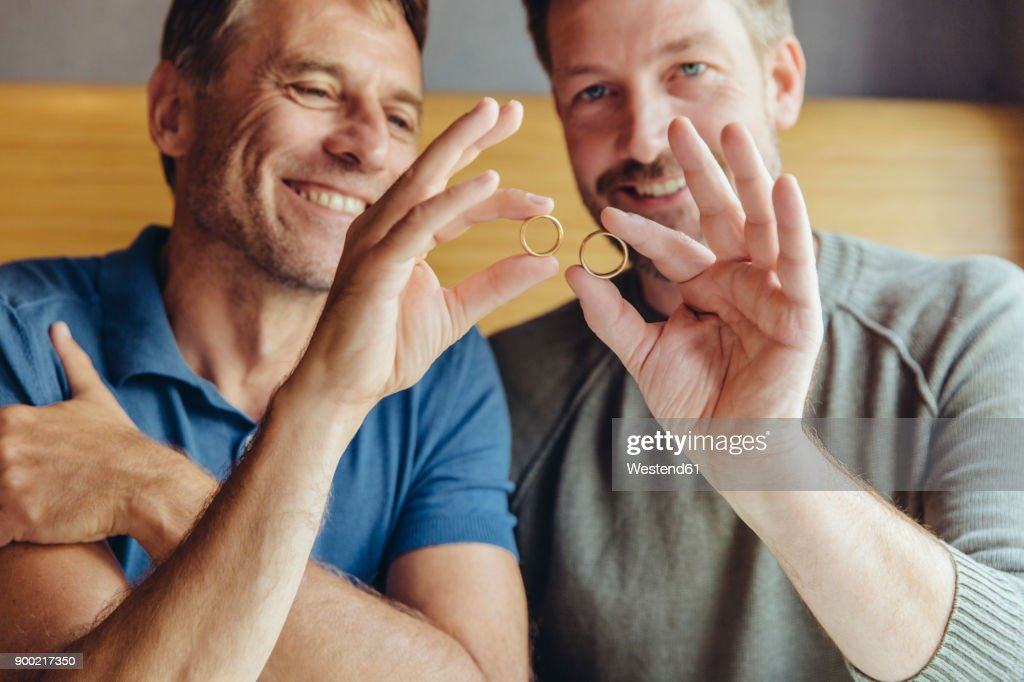 Happy Gay Couple Holding Up Their Wedding Rings Stock Photo Getty
