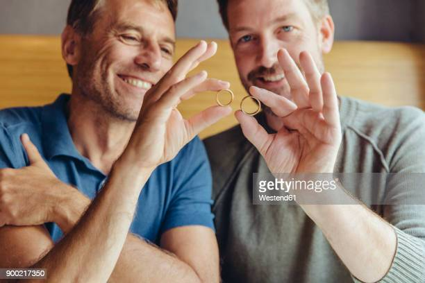 Happy gay couple holding up their wedding rings