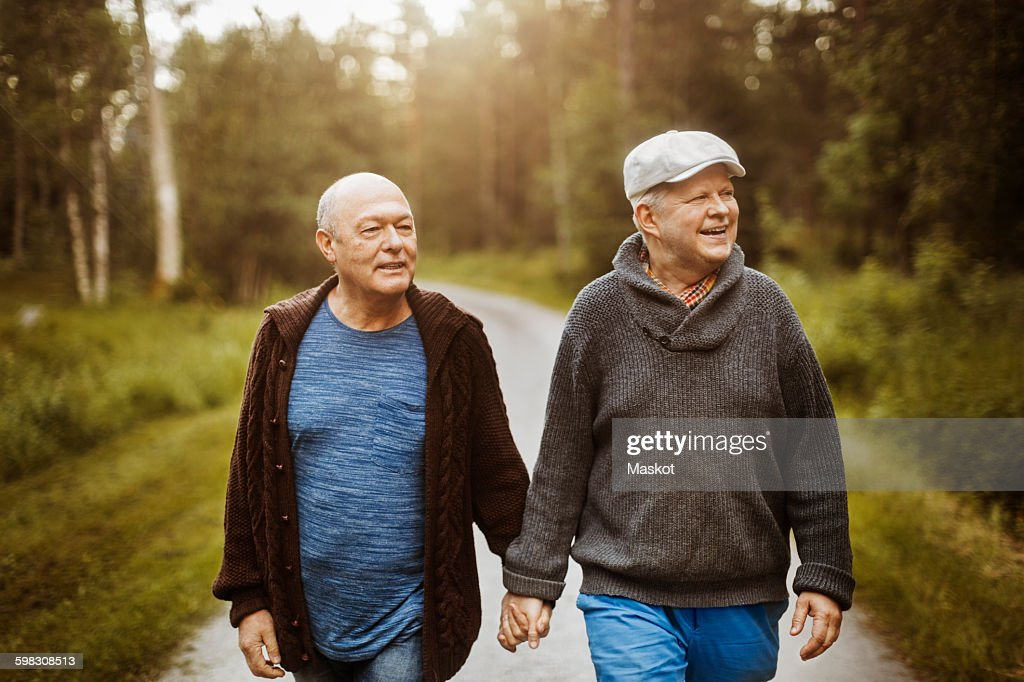 Happy gay couple looking away while walking on road amidst trees : Stock Photo