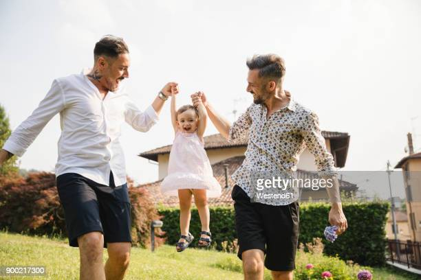 Happy gay couple playing with their child in the garden