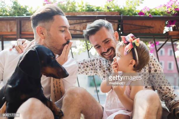 happy gay couple with daughter and dog on balcony - hair bow stock pictures, royalty-free photos & images