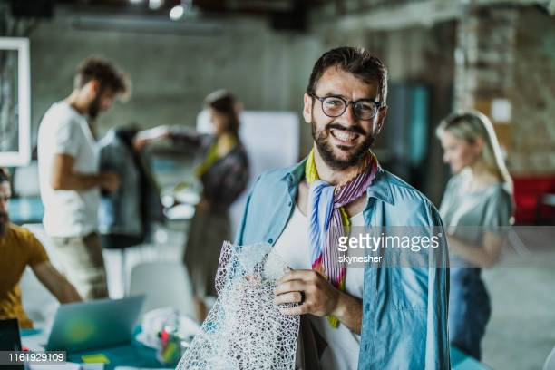happy gay fashion designer in a clothing studio. - fashion designer stock photos and pictures