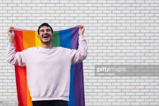 happy gay man with a rainbow flag - bisexuality stock pictures, royalty-free photos & images