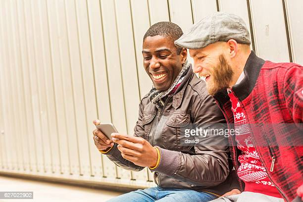 Happy Gay Men Couple Looking at a Mobile Smart Phone
