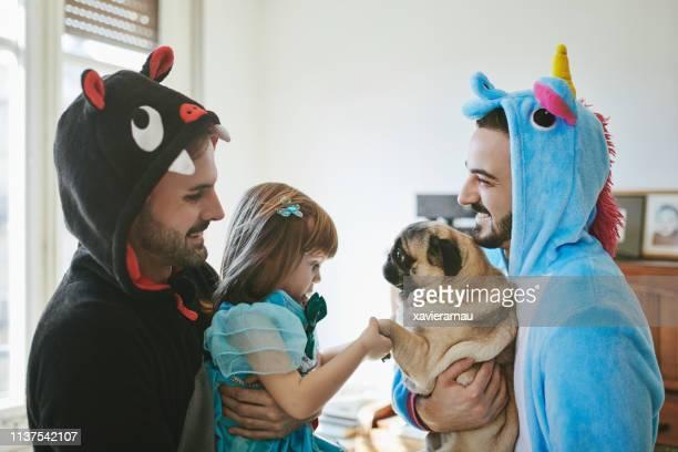 happy gay men in costumes carrying girl and pug - mascara carnaval imagens e fotografias de stock