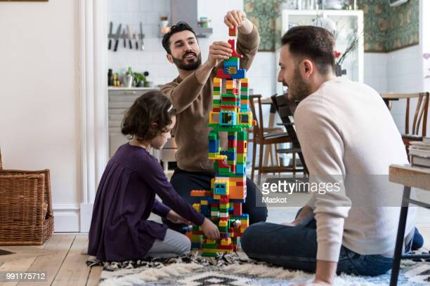 happy gay men playing blocks with daughter at home - social services stock photos and pictures