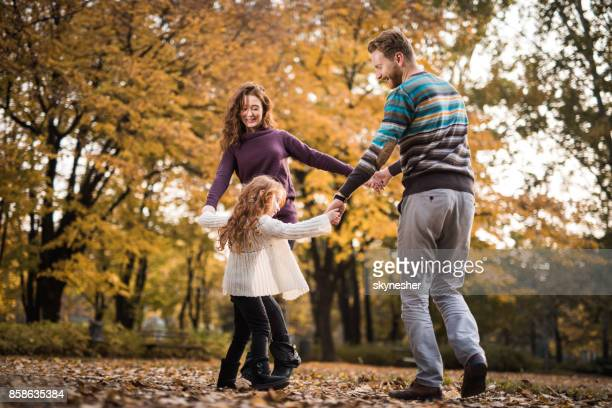happy ginger family playing ring-around-the-rosy during autumn day at the park. - in the park day 3 imagens e fotografias de stock