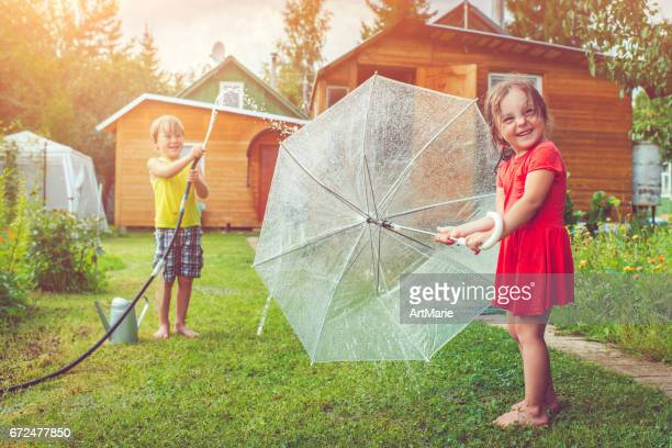 Happy girl and boy playing with sprinkler and umbrella