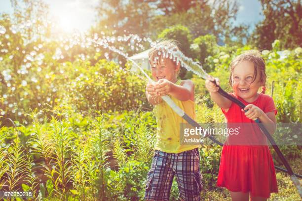 Happy girl and boy playing with water in summer