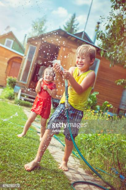 happy girl and boy playing with water in summer - little russian girls stock photos and pictures