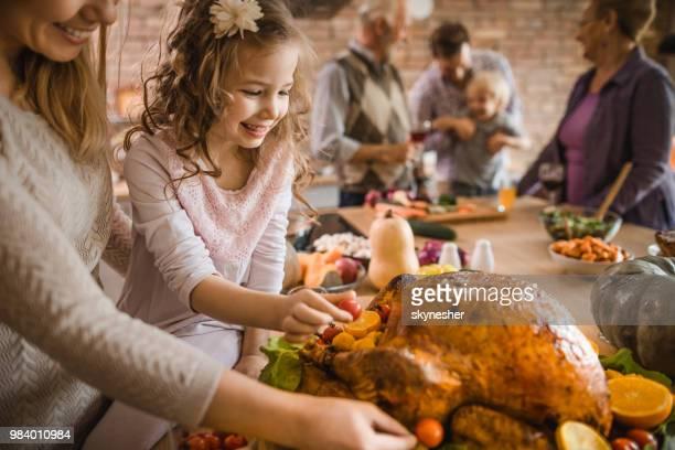 fille heureuse et sa mère prépare le rôti de dinde pour le dîner de thanksgiving. - viande blanche photos et images de collection