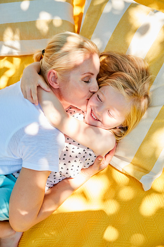 Happy girl and mother hugging and kissing on a blanket - gettyimageskorea