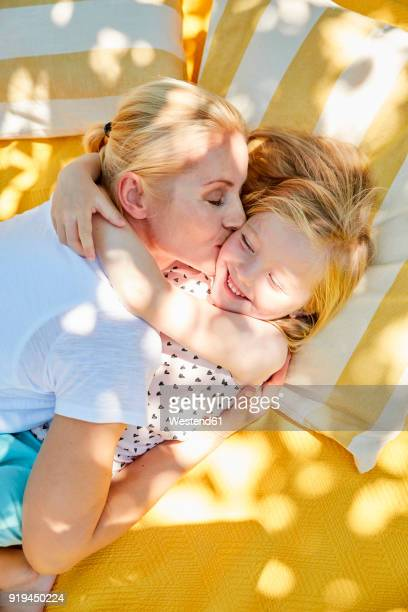 Happy girl and mother hugging and kissing on a blanket