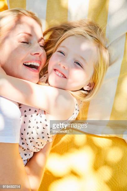 Happy girl and mother hugging on a blanket
