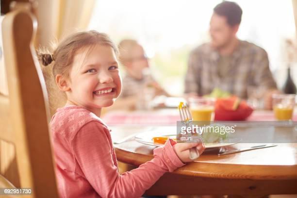 glückliches Mädchen beim Mittagessen