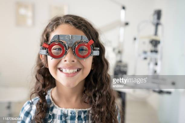 happy girl at the optometrist checking the prescription for her glasses - eye doctor stock pictures, royalty-free photos & images