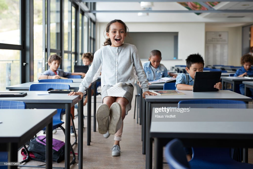 Happy girl balancing between tables with feet in the air in classroom : Stock Photo