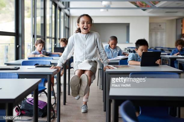 happy girl balancing between tables with feet in the air in classroom - bambino di età scolare foto e immagini stock