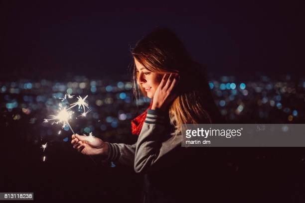 Happy girl by night holding burning sparklers
