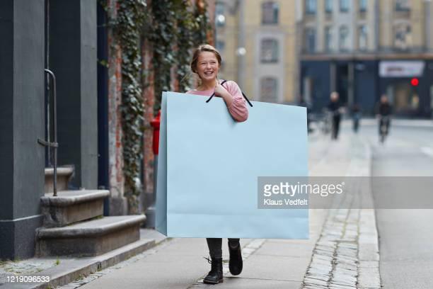happy girl carrying large shopping bag while walking on footpath - tamanho desproporcionado - fotografias e filmes do acervo