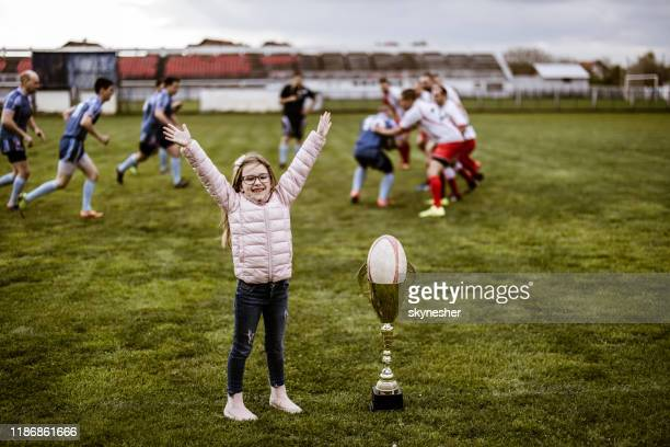 menina feliz que cheering durante o fósforo do rugby no campo de jogo. - tournament champion - fotografias e filmes do acervo