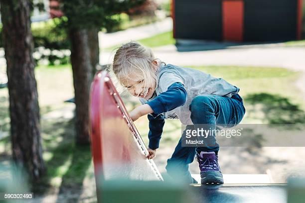 Happy girl climbing slide at yard