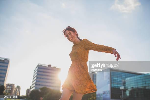glückliches mädchen tanzen in stadt - kleid stock-fotos und bilder