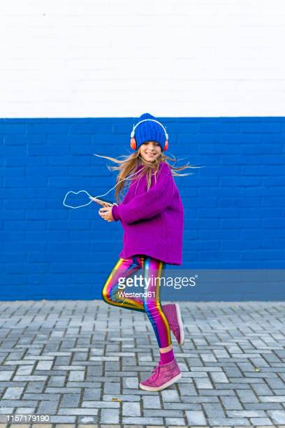 happy girl dancing while listening music with headphones and smartphone - digital native stock pictures, royalty-free photos & images