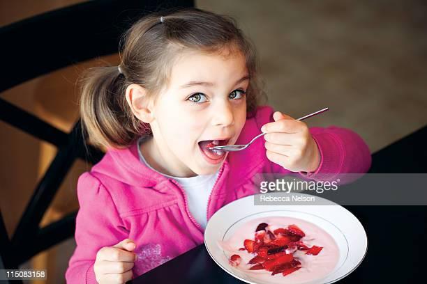 Happy Girl eating breakfast strawberries & yogurt
