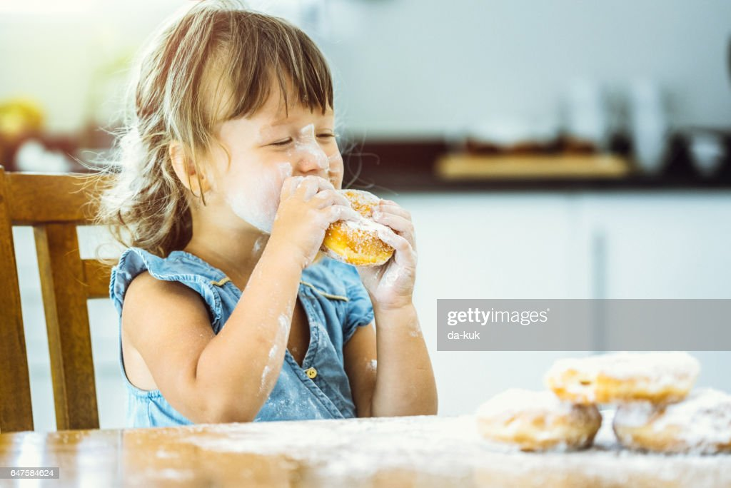 Happy girl eating delicious donut : Stock Photo