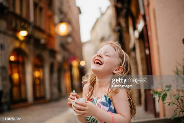 happy girl eating food while standing on street against buildings in city during sunset - innocence stock pictures, royalty-free photos & images