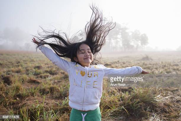 Happy girl enjoying nature on grass meadow on nature field with sunrise. Beauty Girl Outdoor. (Freedom concept)