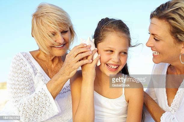 Happy girl enjoying seashell music with grandmother and mother