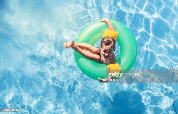Happy girl floating on swim ring in the swimming pool