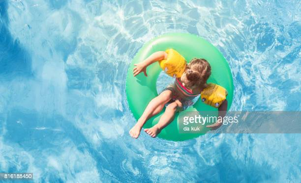 happy girl floating on swim ring in the swimming pool - very young tube stock photos and pictures