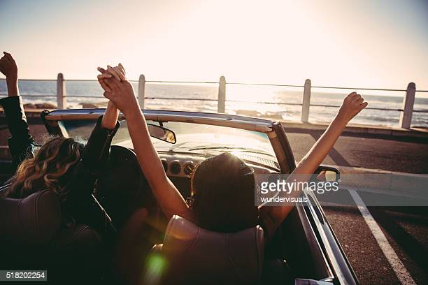 Happy girl friends cheering with raised arms in a convertible