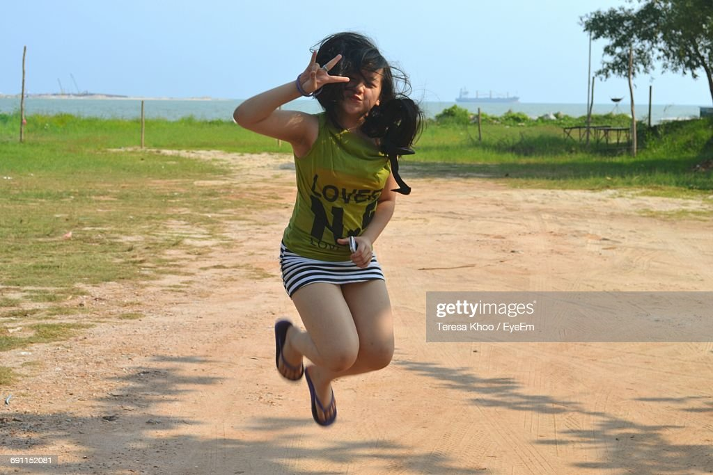 Happy Girl Gesturing While Jumping On Field : Stock Photo