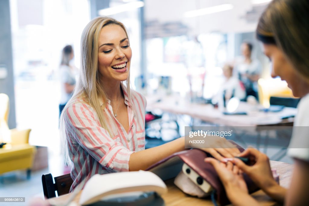 Happy girl getting her nails done at the salon : Stock Photo