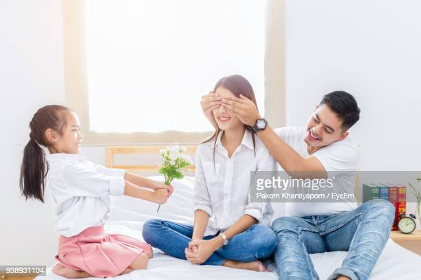 Happy Girl Giving Flower While Smiling Man Closing Eyes Of Sister