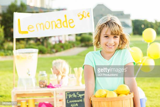 happy girl holding basket of lemons at her lemonade stand - free business coaching stock pictures, royalty-free photos & images