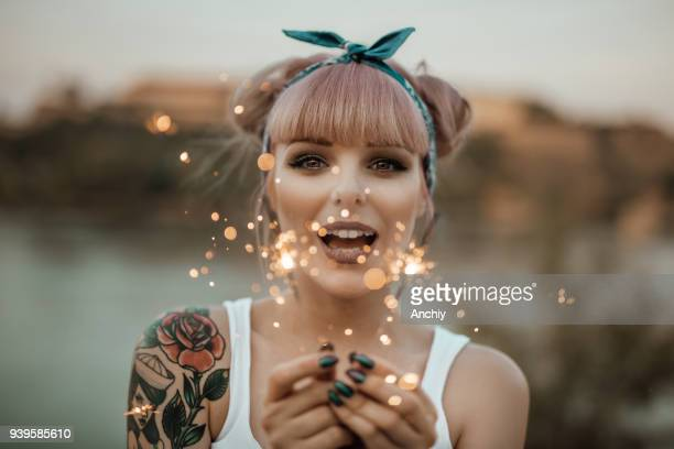happy girl holding burning sparklers - pin up girl stock pictures, royalty-free photos & images