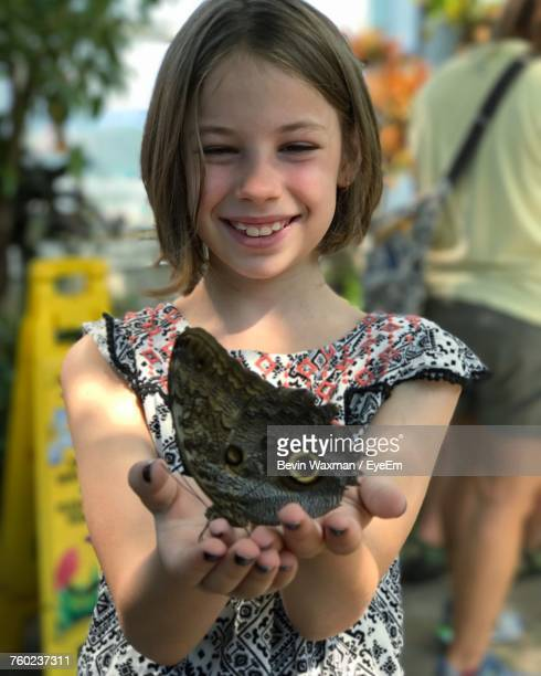 happy girl holding butterfly while standing on footpath - chattanooga stock pictures, royalty-free photos & images