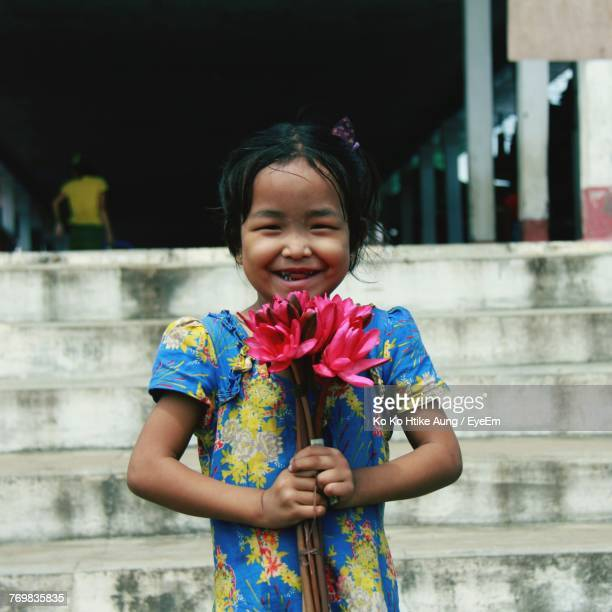 happy girl holding flower - ko ko htike aung stock pictures, royalty-free photos & images