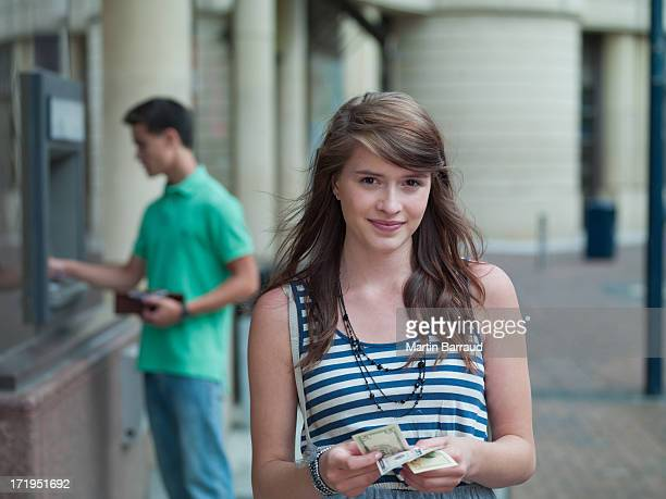 Happy girl holding money near ATM machine
