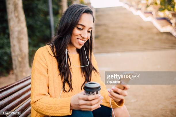 happy girl holding phone and coffee to go - podcasting stock pictures, royalty-free photos & images