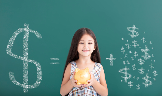 happy girl holding piggy bank and save money concept 1034696628