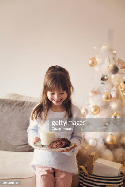 Happy girl holding plate with cookies and milk glass while standing at home