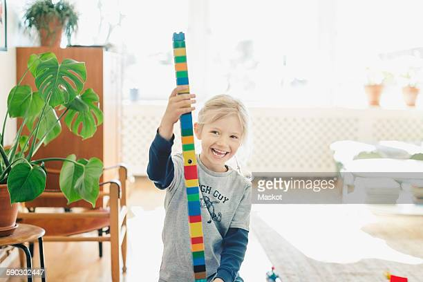 Happy girl holding tower made of toy blocks at home